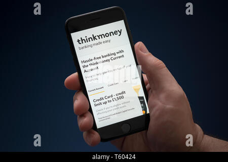 A man looks at his iPhone which displays the Thinkmoney logo (Editorial use only). - Stock Photo