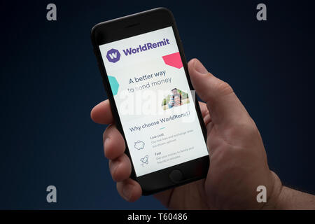 A man looks at his iPhone which displays the WorldRemit logo (Editorial use only). - Stock Photo