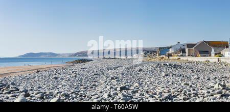 Panoramic view over scenic pebble beach at low tide on bright summer day in Borth, Wales in United Kingdom - Stock Photo
