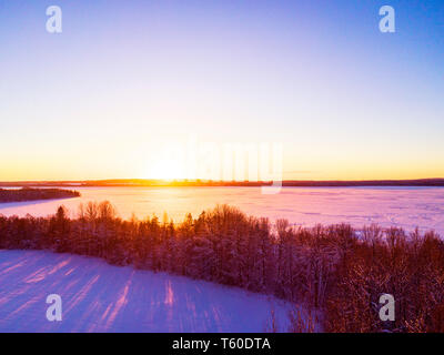 Aerial view of a gold sunset over winter snow-covered pine forest. Winter forest texture. Aerial view. Aerial drone view of a winter landscape. Snow c - Stock Photo