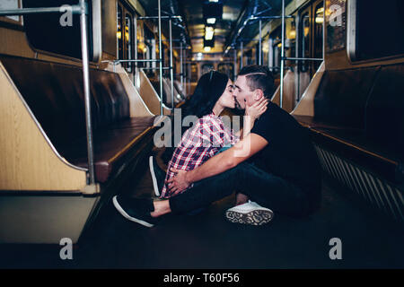 Young man and woman use underground. Couple in subway. Lovely cheerful couple sit together on floor and kissing. Alone in empty underground carriage.  - Stock Photo