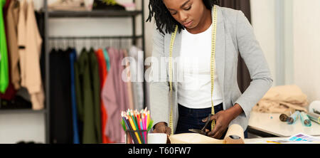 Young tailor cutting drawing, working in studio - Stock Photo