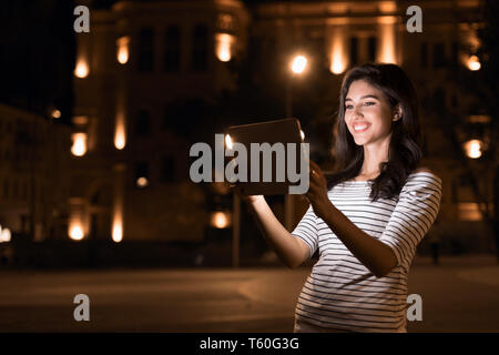 Happy girl making video-call on tablet in night city - Stock Photo