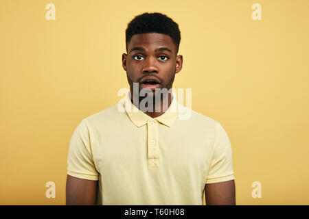 Bearded stylish awesome male having displeased look standing against yellow background., being puzzled, doesn't know what to say,emotion, feeling - Stock Photo