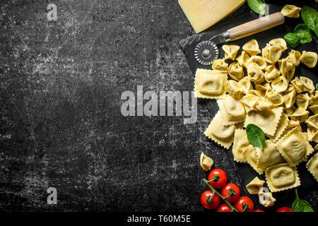 Different types of Italian raw paste on stone Board. On dark rustic background - Stock Photo