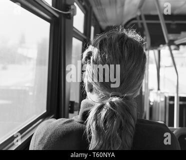 Rear view of a woman on a bus. - Stock Photo