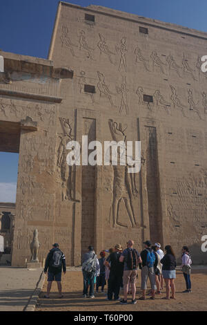 Edfu, Egypt: Tourists and their guide at the first pylon of the temple of Edfu, the largest temple dedicated to Horus and Hathor of Dendera. Stock Photo