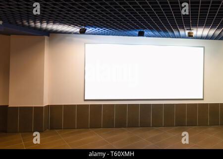 Mock up. Big horizontal blank white billboard on the wall inside building - Stock Photo