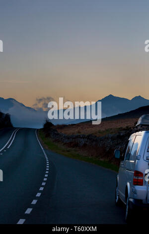 Campervan parked in layby as driver stops to photograph the scenic, twilight view of Mount Snowdon at dusk, Snowdonia National Park, North Wales, UK. - Stock Photo