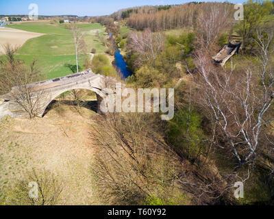 Destroyed railway bridge over Sapina river, Kruklanki town in the background, Poland (former Kruglanken, East Prussia) - Stock Photo