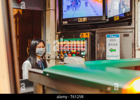 Portrait of taiwanese metro train conductor pressing the button to close the metro train door at a metro station in Taipei - Stock Photo