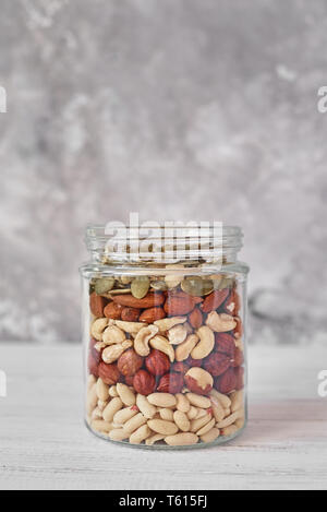 Different types of nuts and seeds in glass jar close up - Stock Photo