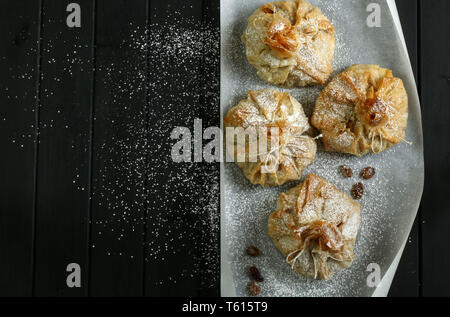 Phyllo pastry strudel with apple filling and sultana grapes, dusted with icing sugar - Stock Photo
