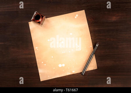 A piece of old paper with an ink pen and an ink well, shot from the top on a dark rustic background with a place for text - Stock Photo