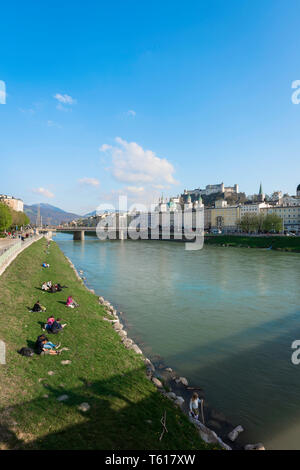 Salzburg summer, view of people relaxing beside the Salzach River in summer with the baroque Old Town (Altstadt) visible in the distance, Austria. - Stock Photo