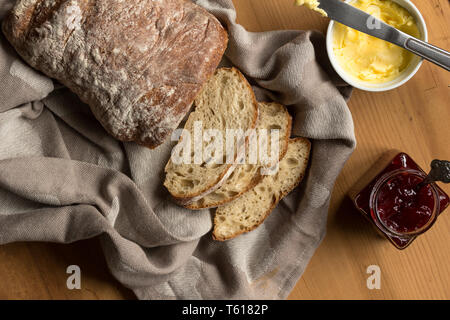 Sourdough bread and slices with butter and knife on kitchen cloth - Overhead image - Stock Photo