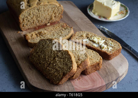 Banana bread loaf with slices and butter  on wooden board on grey background - Stock Photo