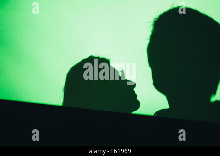 Abstract background shadows of people man and woman on digital wall light from cinema projector on a green wall - Stock Photo