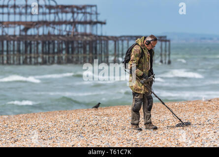Man searching for treasure on a beach using a metal detector in Brighton, East Sussex, England, UK. - Stock Photo