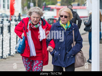Pair of senior women walking outside linking arms. Elderly female friends with arms linked. Senior friendship. - Stock Photo