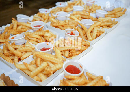 french fried in the paper plate in the row are arranged on the table ready for serve. - Stock Photo