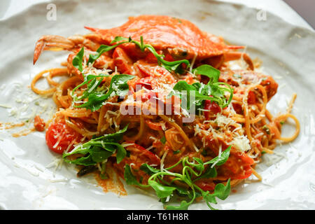 spicy boiled crab spaghetti on white disk with vegetable on top, ready to serve and eat. - Stock Photo