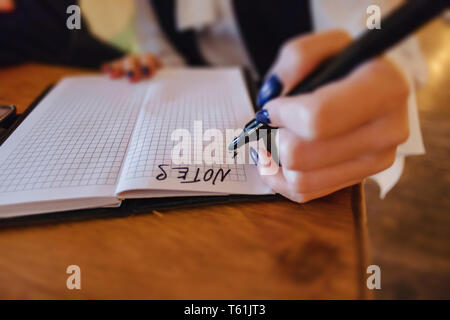 girl is making a note on paper against the background of