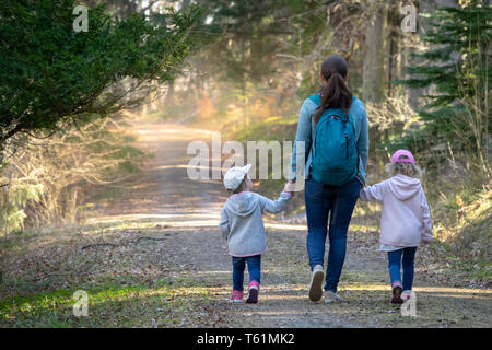 Hiking in the woods. Mother with daughters walking on a path in a sunny forest. Sweden - Stock Photo