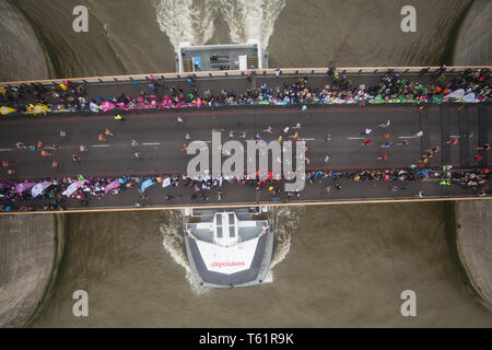 A boat crosses under Tower Bridge as runners take part in the 2019 Virgin Money London Marathon. - Stock Photo