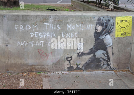 A suspected new Banksy street artwork alongside the image of a child holding the Extinction Rebellion emblem - From this moment despair ends and tacti - Stock Photo