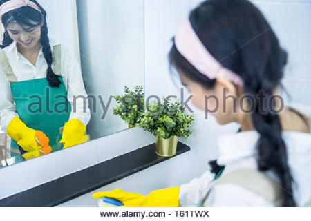 Cleaning wash basin, Woman wear yellow protective rubber gloves with green sponge under running water from a stainless steel tap on a white ceramic ha - Stock Photo
