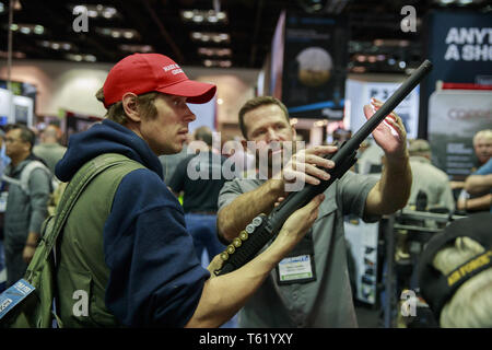 Indianapolis, Indiana, UK. 27th Apr, 2019. An NRA member and Trump supporter wearing a MAGA hat looks at a shotgun during the third day of the National Rifle Association convention. Credit: Jeremy Hogan/SOPA Images/ZUMA Wire/Alamy Live News - Stock Photo