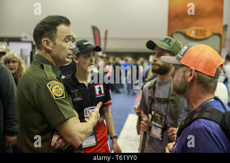 Indianapolis, Indiana, UK. 27th Apr, 2019. A member of the United States Border Patrol speaks with NRA members during the third day of the National Rifle Association convention. Credit: Jeremy Hogan/SOPA Images/ZUMA Wire/Alamy Live News - Stock Photo