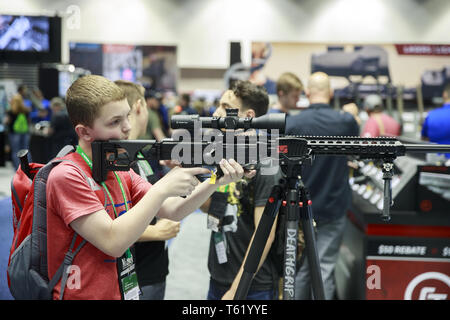 Indianapolis, Indiana, UK. 27th Apr, 2019. A boy looks through the scope of a rifle during the third day of the National Rifle Association convention. Credit: Jeremy Hogan/SOPA Images/ZUMA Wire/Alamy Live News - Stock Photo