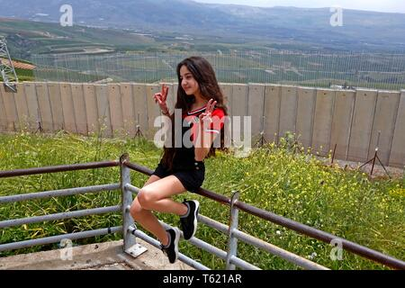 Beirut, Lebanon. 27th Apr, 2019. A Lebanese girl poses for photos with the separation wall along the border with Israel, in southern Lebanon, April 27, 2019. Israel's construction of a wall along its border with Lebanon is a contentious issue between the two countries. Credit: Bilal Jawich/Xinhua/Alamy Live News - Stock Photo