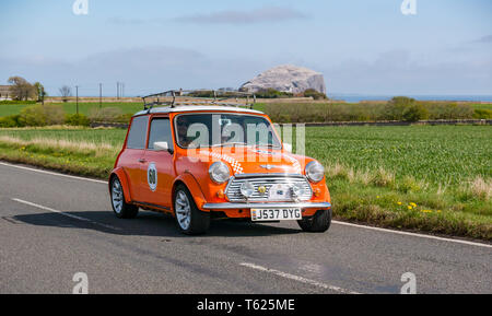 East Lothian, UK. 28 April 2019. Classic Car Tour: North Berwick Rotary Club holds its 3rd rally with 65 classic cars entered. The car rally route is from East Lothian and back through the Scottish Borders, raising money for local charities. A vintage orange 1991 Rover Mini Cooper with Bass Rock in the background - Stock Photo