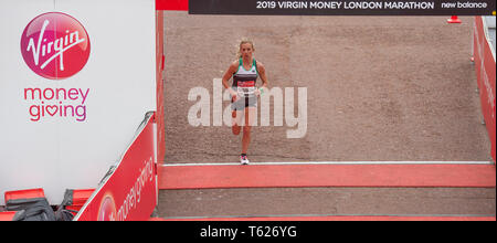 London, UK. 28th April, 2019. The London Marathon race finishes on The Mall in Westminster. Image: Emily Sisson (USA) comes over the finish line in the Elite Womens Marathon in 2:23:08. Credit: Malcolm Park/Alamy Live News. - Stock Photo