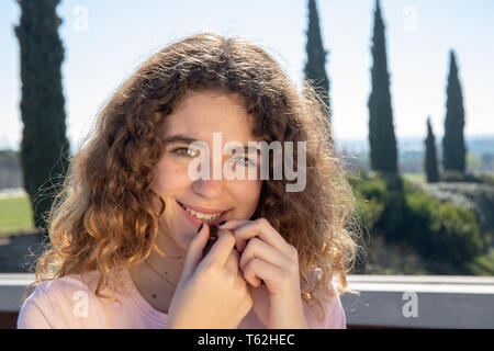 Portrait of a pre-adolescent girl posing in a public park on a sunny spring day - Stock Photo