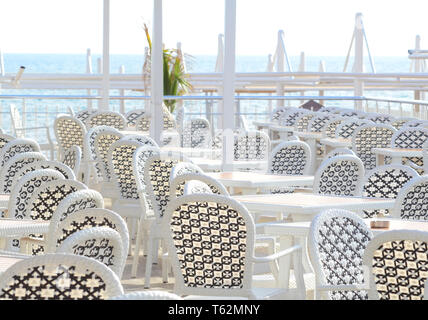White plastic furniture in a cafe on the coast before the start of the beach season - Stock Photo