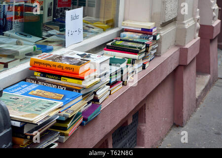 Pile of old German used books for sale on windowsill of used goods store - Stock Photo
