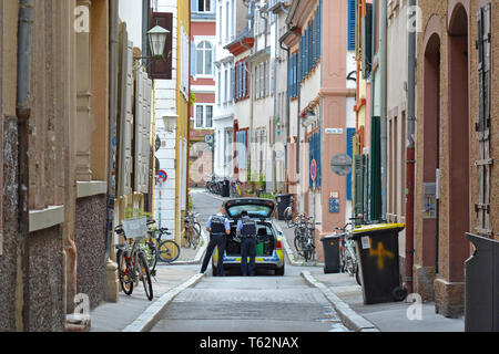 Police car with two officers on patrol in side street of historical city center of Heidelberg in Germany - Stock Photo