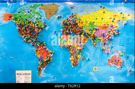 Push pins marking locations on a world map. - Stock Photo