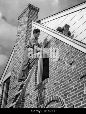 1940s WORKMAN ON STEPLADDER FITTING A NEW WINDOW ON BRICK HOUSE - b11694 HAR001 HARS RESIDENTIAL MALES RISK BUILDINGS PROFESSION CONFIDENCE B&W SKILL OCCUPATION SKILLS PROPERTY STRENGTH CAREERS EXTERIOR FITTING KNOWLEDGE LABOR EMPLOYMENT HOMES OCCUPATIONS REAL ESTATE CONCEPTUAL STRUCTURES RESIDENCE EDIFICE EMPLOYEE STEPLADDER YOUNG ADULT MAN BLACK AND WHITE CAUCASIAN ETHNICITY HAR001 INSTALLING LABORING OLD FASHIONED - Stock Photo