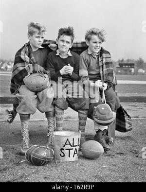 1940s THREE BOYS SITTING ON BENCH WRAPPED IN BLANKET HOLDING  FOOTBALL HELMETS WATCHING GAME FACIAL EXPRESSIONS AND GESTURES - b13536 HAR001 HARS BENCH STRESS NOSTALGIC GAMES PAIR SUBURBAN URBAN DEPRESSION EXPRESSION OLD TIME NOSTALGIA BROTHER OLD FASHION 1 JUVENILE FACIAL BLANKET TEAMWORK COMPETITION ATHLETE PLEASED JOY LIFESTYLE CELEBRATION WINNING BROTHERS MOODY HEALTHINESS COPY SPACE FULL-LENGTH PHYSICAL FITNESS INSPIRATION MALES TEENAGE BOY ATHLETIC SNEAKERS SIBLINGS EXPRESSIONS TROUBLED PLAYERS B&W SADNESS EYE CONTACT DREAMS HAPPINESS CHEERFUL ANXIOUS STRENGTH COURAGE AND EXCITEMENT - Stock Photo