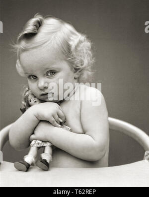 1940s WARY BLOND CURLY HAIR LITTLE GIRL SITTING IN CHAIR HUGGING TOY DOLL LOOKING AT CAMERA - b19272 HAR001 HARS FEMALES HOME LIFE COPY SPACE HALF-LENGTH CARING RISK AFRAID EXPRESSIONS B&W SADNESS PROTECTIVE PROTECTION CURLY IN FEARFUL SHY JUVENILES MISERABLE RETICENT WARY BABY GIRL BLACK AND WHITE CAUCASIAN ETHNICITY CLUTCHING HAR001 OLD FASHIONED - Stock Photo