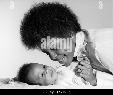 1970s SMILING AFRICAN AMERICAN MOTHER HOLDING HAND AND LOOKING AT HAPPY BABY DAUGHTER LYING ON HER BACK - b24811 HAR001 HARS OLD FASHION 1 JUVENILE FACIAL YOUNG ADULT INFANT STRONG PLEASED JOY LIFESTYLE FEMALES HEALTHINESS HOME LIFE DAUGHTERS PERSONS INSPIRATION CARING SERENITY CONFIDENCE EXPRESSIONS B&W HAPPINESS HEAD AND SHOULDERS CHEERFUL STRENGTH AFRICAN-AMERICANS AFRICAN-AMERICAN AND BLACK ETHNICITY PRIDE AT ON SMILES JOYFUL STYLISH PERSONAL ATTACHMENT AFFECTION EMOTION GROWTH JUVENILES MOMS TOGETHERNESS YOUNG ADULT WOMAN AFRO HAIR STYLE BABY GIRL BLACK AND WHITE HAR001 OLD FASHIONED - Stock Photo