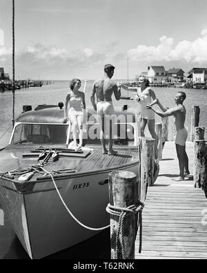 1940s 1950s TWO YOUNG COUPLES MEN WOMEN WEARING BATHING SUITS BOARDING SMALL CABIN CRUISER POWER BOAT MOORED BAY SIDE AT DOCK - b5270 HAR001 HARS LIFESTYLE FEMALES MARRIED RURAL SPOUSE HUSBANDS HEALTHINESS LUXURY COPY SPACE FRIENDSHIP FULL-LENGTH LADIES PERSONS DOCK MALES CONFIDENCE TRANSPORTATION B&W PARTNER TIME OFF SKILL ACTIVITY AMUSEMENT HAPPINESS ADVENTURE HOBBY LEISURE TRIP INTEREST GETAWAY EXCITEMENT HOBBIES KNOWLEDGE RECREATION PASTIME PLEASURE AT HOLIDAYS NJ POWER BOAT CONCEPTUAL BOATING STYLISH NEW JERSEY BATHING SUIT RELAXATION SEASHORE TOGETHERNESS VACATIONS WIVES YOUNG ADULT MAN - Stock Photo