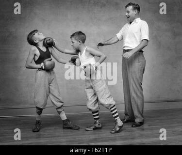 1930s TWO BOYS SPARRING PUNCHING WEARING BOXING GLOVES  ATHLETIC OUTFITS ADULT MAN ACTING AS REFEREE - b8259 HAR001 HARS ATHLETICS COPY SPACE FULL-LENGTH PHYSICAL FITNESS PERSONS MALES RISK ATHLETIC ACTING B&W ADVENTURE PROTECTION STRENGTH EXCITEMENT OUTFITS RECREATION PUNCHING CONNECTION ATHLETES COOPERATION JUVENILES MID-ADULT MID-ADULT MAN SPAR SPARRING BLACK AND WHITE CAUCASIAN ETHNICITY HAR001 OLD FASHIONED - Stock Photo