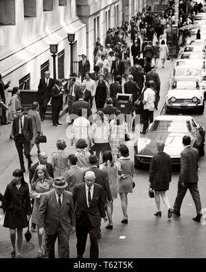 1970s CITY STREET FULL OF MEN AND WOMEN WORKERS  WALKING  CROSSING THE STREET COMMUTING - c10918 HAR001 HARS PEDESTRIANS TRANSPORTATION B&W GATHERING HIGH ANGLE AND AUTOS CONGESTED COMMUTING OCCUPATIONS AUTOMOBILES VEHICLES COOPERATION THRONG BLACK AND WHITE CAUCASIAN ETHNICITY HAR001 OLD FASHIONED - Stock Photo