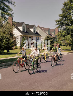 1960s 1970s GROUP CHILDREN RIDING BIKES DOWN SUBURBAN STREET - kb7278 HAR001 HARS BIKES SUMMERTIME NEIGHBORS PRETEEN BOY HAPPINESS NEIGHBORHOOD AFRICAN-AMERICANS AFRICAN-AMERICAN CONNECTION 7 PEDDLING COOPERATION JUVENILES PRE-TEEN PRE-TEEN BOY PRE-TEEN GIRL TOGETHERNESS CAUCASIAN ETHNICITY HAR001 OLD FASHIONED AFRICAN AMERICANS - Stock Photo